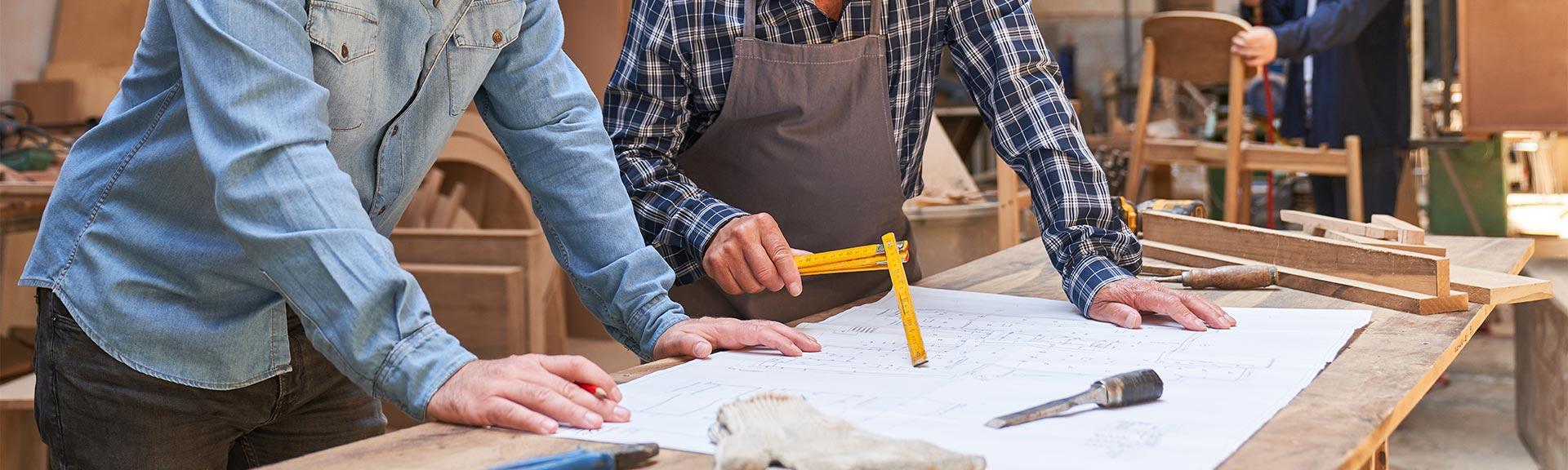 Handwerker und Tischlerauszubildender diskutieren über einen Bauprojekt-Entwurf